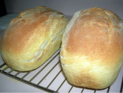 two loaves of bread cooling on a rack