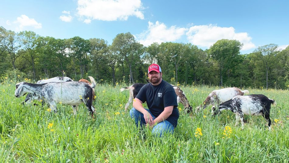Jonas Asbill in a field with goats