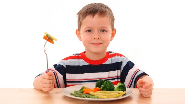 Boy eating plate of vegetables.