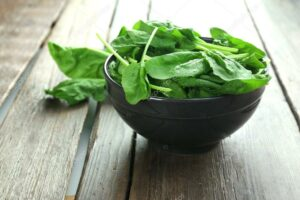 Fresh spinach in a wooden bowl on a wooden table